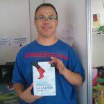 """Agustín posando con la novela """"Fotografiar la lluvia"""""""
